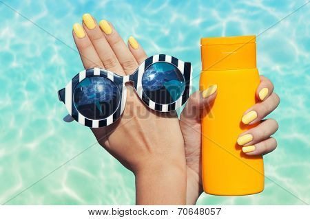 Summer fashion and beauty hand care concept, woman at the pool holding sunglasses and sunscreen lotion