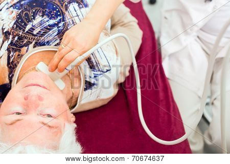 Female doctor testing thyroid of senior patient with surgery ultrasonic device