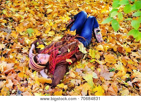 Happy woman portrait lying on autumn leaves in park and looking at camera.