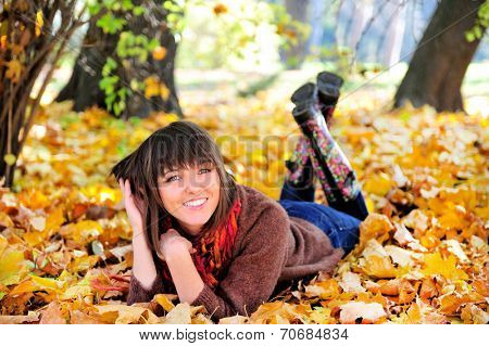 Happy cute woman outdoor portrait, lying in autumn park.