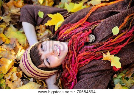 Smiling happy girl in knitted striped hat lying in autumn leaves. Close up portrait, outdoor.