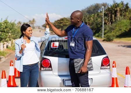 happy african girl and driving instructor doing high five after getting her driving license