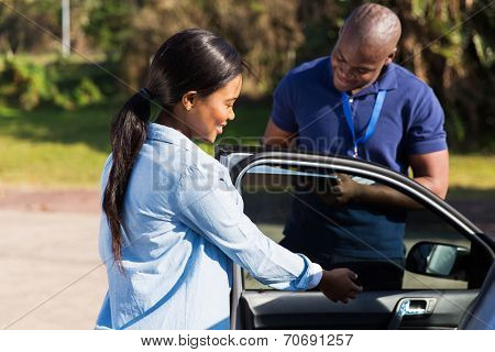 happy female african learner driver with instructor doing pre driving inspection
