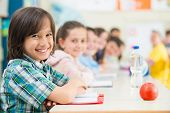 Cheerful kids learning in school classroom poster