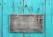 Blank distressed sign with rugged wooden cross hanging by rope on antique teal blue wood background poster