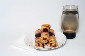 Rolled Pancakes With Strawberry Jam And A Glass Of Water