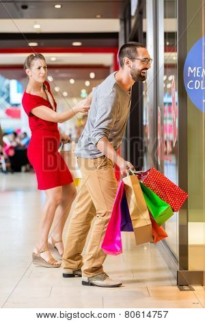 Couple at shop window in mall shopping