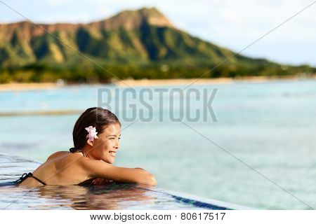 Hawaii beach travel vacation woman swimming relaxing at luxury pool hotel resort. Asian young adult on Waikiki beach, Honolulu, Oahu on exotic holidays