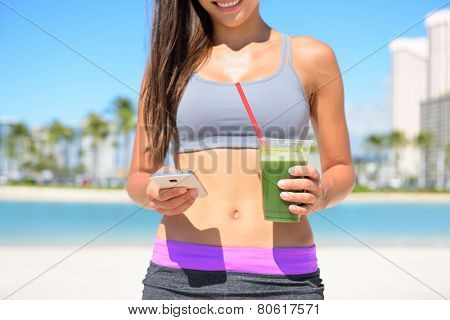 Woman drinking vegetable Green detox smoothie after fitness running workout on summer day. Fitness and healthy lifestyle concept with beautiful fit mixed race Asian Caucasian model.