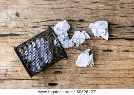 A Lot Of Wrinkled Paper Laying In And Around A Wastepaper Basket.