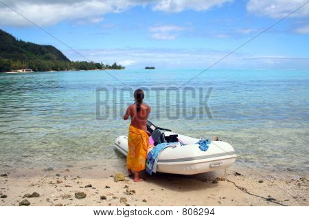 topless woman on the beach aside an inflatable boat