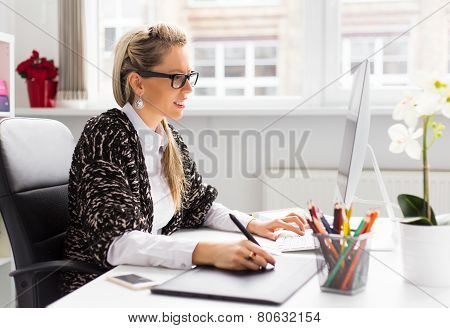 Young female designer using graphics tablet