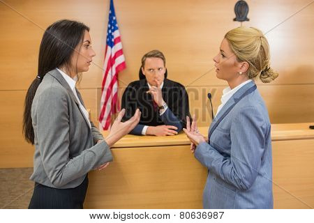 Lawyers speaking with the judge in the court room