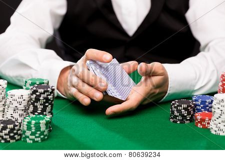 casino, gambling, poker, people and entertainment concept - close up of holdem dealer shuffling playing cards deck and chips on green table