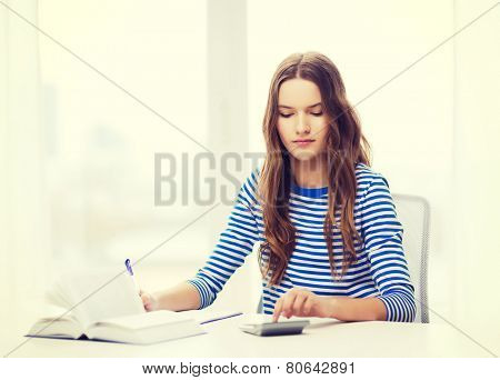 education and home concept - concecntrated student girl with notebook, calculator and book