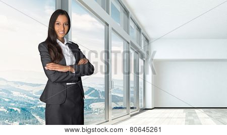 Confident professional female estate agent or broker with a friendly smile in an empty office or apartment with a large open-plan bright white room with panoramic view windows overlooking countryside