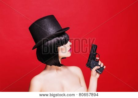 fashion beautifull model with pistol in hat, on red background