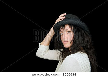 Beautiful woman wearing a hat on a black background.