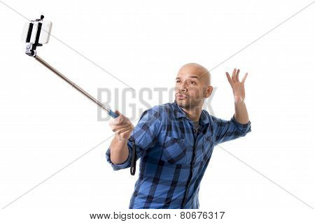 young Hispanic man in casual shirt having fun shooting mobile phone selfie picture or recording video holding stick playing with face expression isolated on white background poster