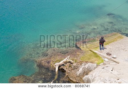Perspective of a fisherman angling on seashore. poster