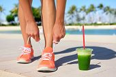 Running woman runner with green vegetable smoothie.  Fitness and healthy lifestyle concept with female model tying running shoe laces. poster