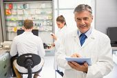 Senior pharmacist using tablet pc at the hospital pharmacy poster
