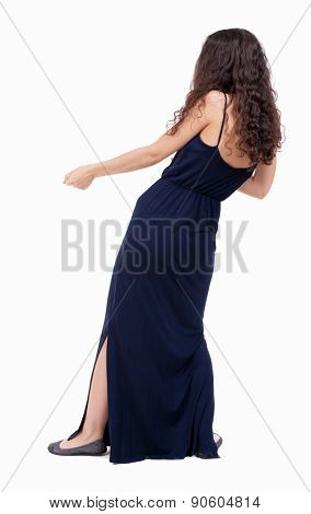 back view of standing woman pulling a rope from the top or cling to something.  Rear view people collection.  backside view of person. Woman in evening dress pulling a rope from the bottom.