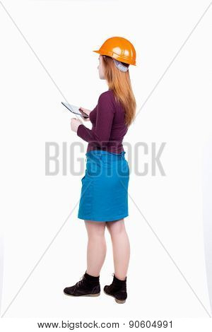 Backview of business woman in construction helmet stands and enjoys tablet or using a mobile phone. Standing young girl. Rear view people collection.  Engineer scorekeeper at work.