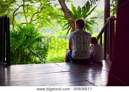 Father And Son Sitting On Tree House Stairs In Tropical Forest