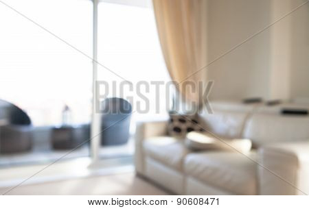 Interior blur background. Living room with big window, sofa, tree