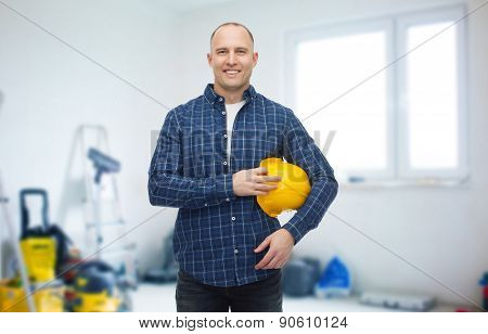 repair, building, construction and maintenance concept - smiling man holding helmet over storeroom background