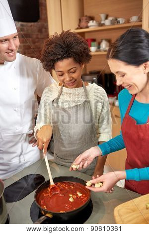 cooking class, culinary, food and people concept - happy group of women and male chef cook cooking tomato souse in kitchen poster