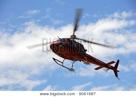 Red helicopter landing against blue sky