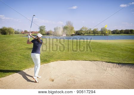 Female golf player hitting ball in sand bunker, with flag on green and lake in background.