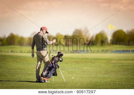 Male golf player taking out golf club from bag, with green and flag in background.