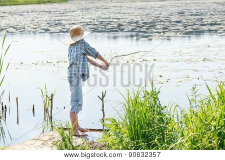 Full Length Boy's Portrait Is Throwing Bait Of Fishing Rod