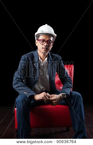 Face Of 45S Years Old Asian Man Wearing White Safety Helmet Sitting On Red Sofa Against Dark Backgro
