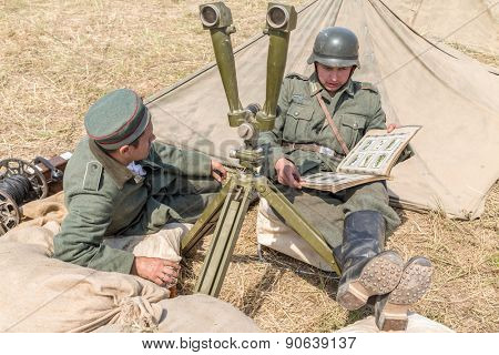 NELIDOVO, RUSSIA- JULY 12, 2014: Battlefield 2014: two Nazi soldiers watching photo album beside the periscope