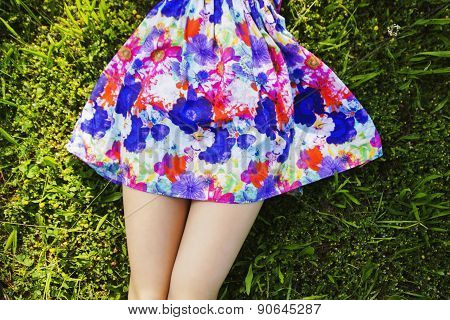 Legs and colorful skirt of girl lying in the grass poster