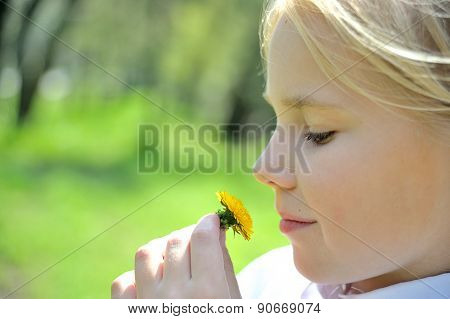Profile of cute girl with  dandelion looking at it in the park