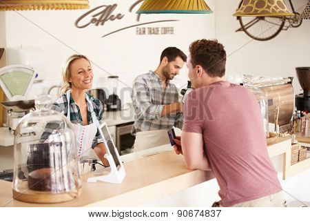 Young man paying for his order in a cafe