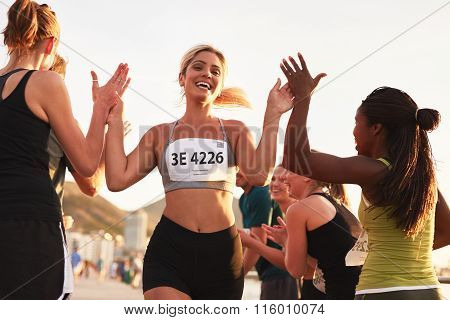 Multi ethnic group of young adults cheering and high fiving a female athlete crossing finish line. Sportswoman giving high five to her team after finishing the race. poster