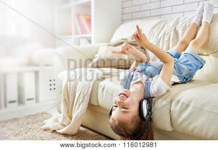 little girl with headphones at home. child girl listening to music.