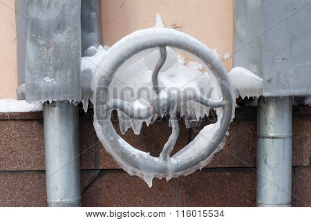 Frozen rudder mechanism, water tap. icy surface with icicles. soft focus