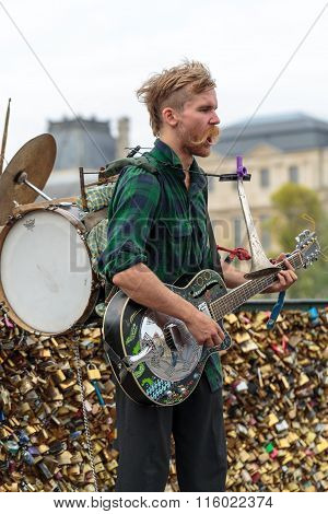 PARIS FRANCE - SEPTEMBER 11 2014: A street musician busker entertain public on Pont des Arts in Paris France