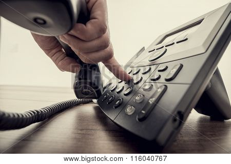 Male Hand Holding Telephone Receiver And Dialing A Phone Number