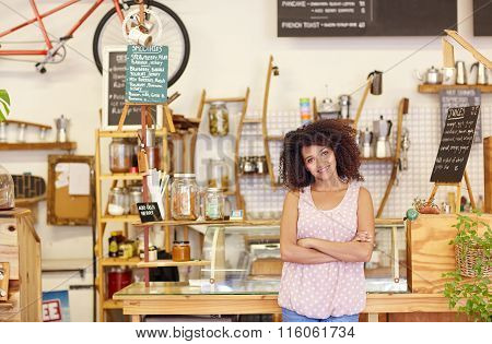 Small business owner standing proudly in her coffee shop