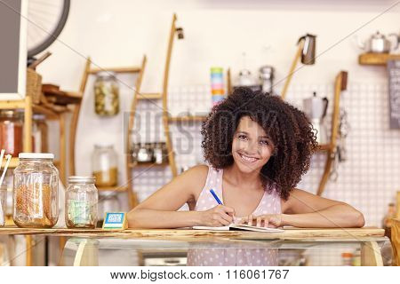 Young woman writing an order in her coffee shop
