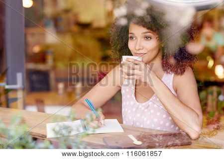 Beautiful woman gazing out a coffee window daydreaming