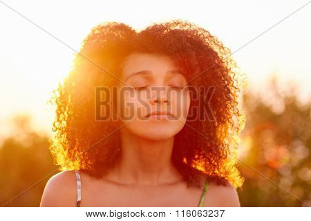Curly hair woman closing her eyes on summer evening